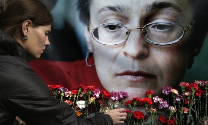 A woman places flowers before a portrait of slain Russian journalist Anna Politkovskaya, in Moscow, on Oct. 7, 2009. (AP Photo/Pavel Golovkin)