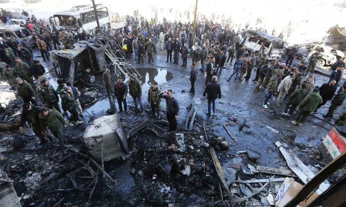 Syrian pro-government forces and residents gather at the site of suicide bombings in the area of a revered Shiite shrine in the town of Sayyida Zeinab, on the outskirts of the capital Damascus, on Jan. 31, 2016. The Islamic State group claimed responsibility for the bombings that killed at least 45 people. (Louai Beshara/AFP/Getty Images)