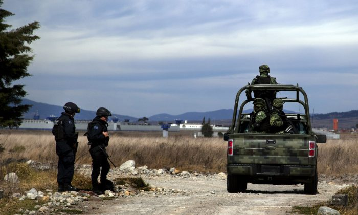 """Federal Police and soldiers patrol on the perimeters of the Altiplano maximum security prison in Almoloya, west of Mexico City, Saturday, Jan. 9, 2016, where Joaquin """"El Chapo"""" Guzman, head of the Sinaloa drug cartel, is being held after his recapture on Friday. Guzman was sent back to the maximum-security prison from where he escaped last July 11 through an elaborate tunnel that was dug to shower stall. (AP Photo/Marco Ugarte)"""