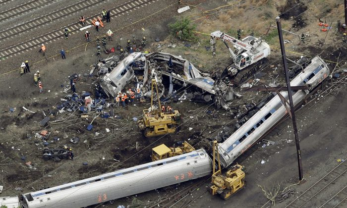 In this May 13, 2015 file photo, emergency personnel work at the scene of a derailment in Philadelphia of an Amtrak train headed to New York. A federal accident investigations board is set to release documents Feb. 1, 2016, that could shed light on the cause of a fatal Amtrak train derailment in Philadelphia last year. The National Transportation Safety Board has wrapped up its investigative phase into the crash that killed eight people and injured about 200 others. The board is now releasing factual information gathered so far. (AP Photo/Patrick Semansky, File)