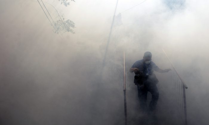 A man walks through the fumes as Health Ministry employees fumigate against the Aedes aegypti mosquito to prevent the spread of the Zika virus in Soyapango, 6 kilometers east of San Salvador, on Jan. 21, 2016. (Marvin Recinos/AFP/Getty Images)