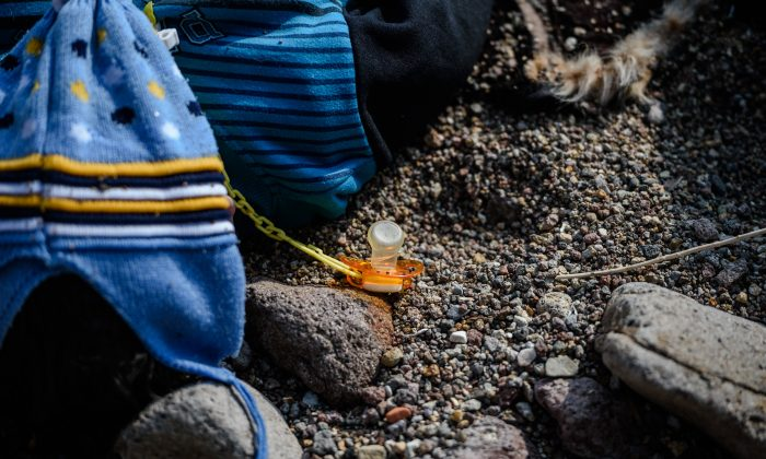 A baby pacifier lies next to the body of a child on a beach in Canakkale's Bademli District on Jan. 30, 2016 after at least 37 migrants drowned when their boat sank in the Aegean Sea while trying to cross from Turkey to Greece. (Ozan Kose/AFP/Getty Images)