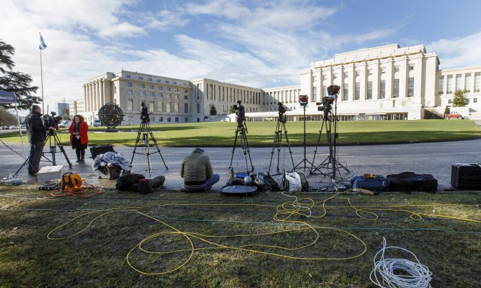 Reporters wait in front the U.N. building after Syria talks were rescheduled at the European headquarters of the United Nations in Geneva, Switzerland, on Feb. 1, 2016. A spokeswoman for U.N. envoy Staffan de Mistura says indirect talks between the Syrian government and the opposition are likely to be delayed. (Salvatore Di Nolfi/Keystone via AP)
