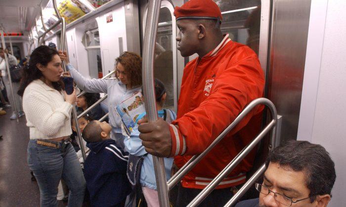 Guardian Angel Eric Jackson, right, looks around while patrolling a subway car in New York, Thursday, June 19, 2003. (AP Photo/Bebeto Matthews)