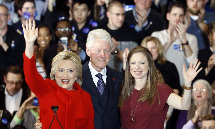 Democratic presidential candidate Hillary Clinton, from left, former President Bill Clinton and daughter Chelsea acknowledge supporters during a caucus night rally at Drake University in Des Moines, Iowa, Monday, Feb. 1, 2016. Sticker Kid can be seen in the top left. (AP Photo/Patrick Semansky)