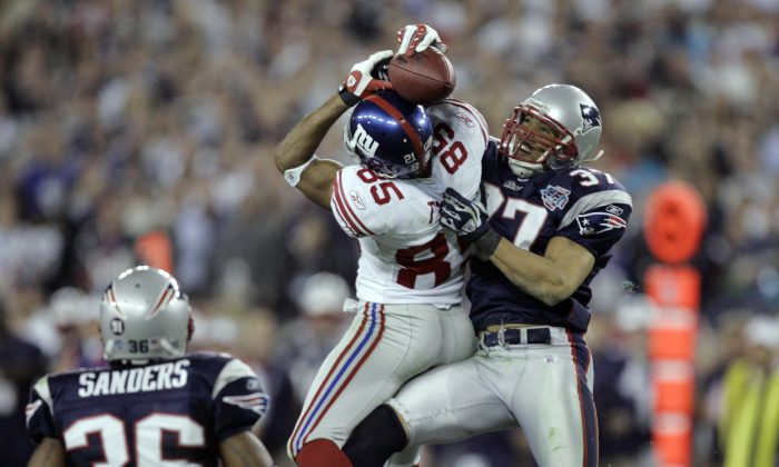 David Tyree's (C) 32-yard catch while in the clutches of Rodney Harrison (R) helped the New York Giants defeat the New England Patriots 17–14 in Super Bowl XLII. (AP Photo/Gene Puskar)