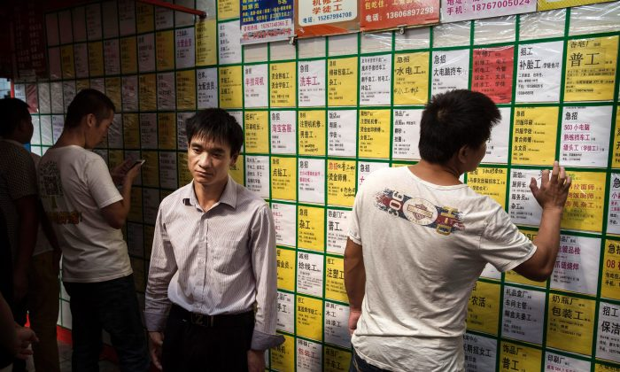 Men look at job postings on a bulletin board at a centre in Yiwu in Zhejiang Province, China on Sept. 18, 2015. (Kevin Frayer/Getty Images)