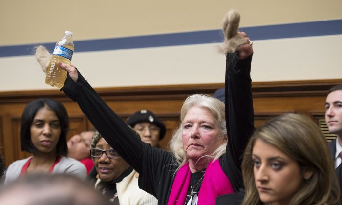 Flint, Mich. resident Glaydes Williamson holds up water from Flint and hair pulled from her drain, during the House Oversight and Government Reform Committee hearing to examine the ongoing situation in Flint, Mich., on Capitol Hill in Washington, D.C., on Feb. 3, 2016. Michigan should have required the city of Flint to treat its water for corrosion-causing elements after elevated lead levels were first discovered in the city's water a year ago, the state's top environmental regulator says in testimony prepared for congressional hearing. (AP Photo/Molly Riley)