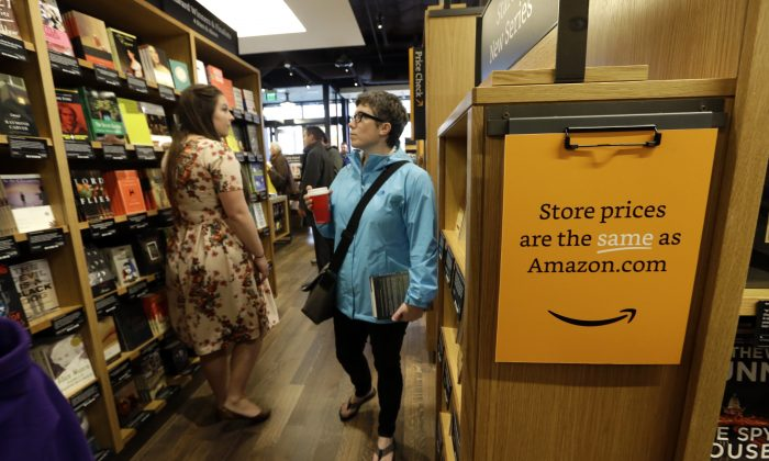 Customers browse aisles at the opening day for Amazon Books, the first brick-and-mortar retail store for online retail giant Amazon, Tuesday, Nov. 3, 2015, in Seattle. (AP Photo/Elaine Thompson)