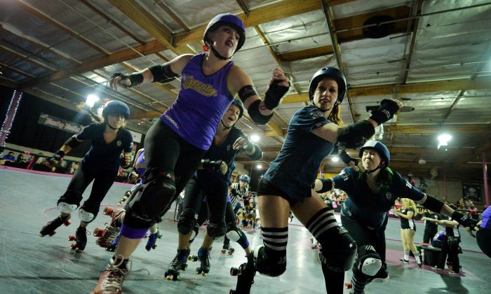 Members of the Sirens team (blue uniforms) compete against the Varsity Brawlers (purple uniforms) during the L.A. Derby Dolls women's banked track roller derby event in Los Angeles on September 27, 2014. (MARK RALSTON/AFP/Getty Images)