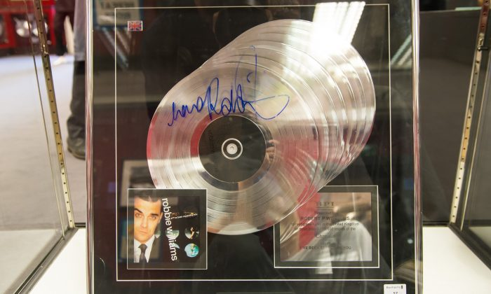 "A multi platinum award for the album ""I've Been Expecting You"" signed by Robbie Williams is seen at the press review before the auction of Robbie Williams memorabilia in aid of the Donna Louise Children's Hospice at Bonhams on July 15, 2015 in London, England.  (Ian Gavan/Getty Images)"