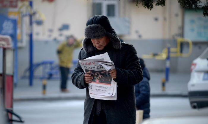 """A man reads a newspaper with a front page headline that reads  """"China's GDP grows at 6.9 percent""""  in Beijing on Jan. 19, 2016. China's economy grew at its slowest pace in a quarter of a century last year as it undergoes a difficult transition. (WANG ZHAO/AFP/Getty Images)"""