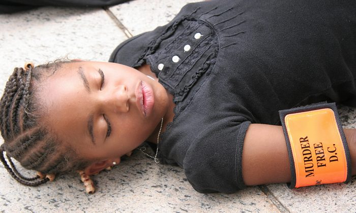 "Radiance Hunter, 9-years-old lies ""dead"" in protest 24 July, 2007 during a protest outside the US District Courthouse in Washington, DC. (Karen Bleier/AFP/Getty Images)"