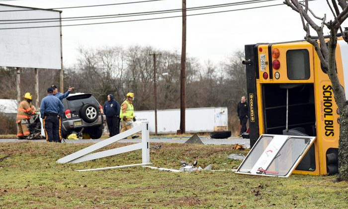 Emergency personnel respond to the scene of an accident involving a school bus and SUV in Fairfield Township, N.J., on Thursday Jan. 4, 2016.   One person is dead and four children hurt after an SUV and a school bus carrying special needs students collided in southern New Jersey. State police say the SUV driver was pronounced dead at the scene Thursday morning. The students on board the Bridgeton Public Schools bus suffered minor injuries.  (Dave Griffin/The Press of Atlantic City via AP)