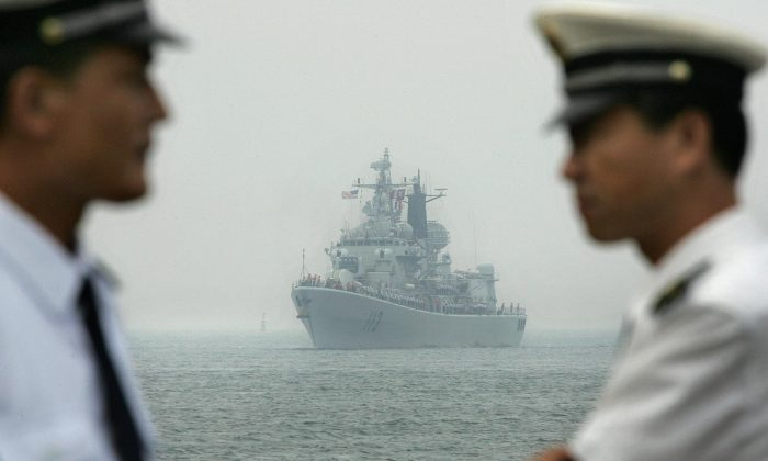 Chinese Navy officers wait dockside as a Chinese Navy warship escorting the arrival of the USS Curtis Wilbur (DDG54) arrives at Qingdao port, in Qingdao, in eastern China's Shandong Province, on Sept. 13, 2005. (Frederic J. Brown/AFP/Getty Images)