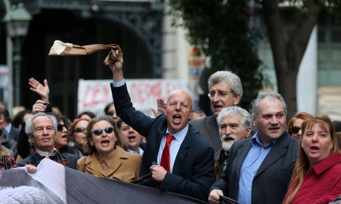 Protesting lawyers shout slogans as their colleague holds up during a 24-hour nationwide general strike in Athens, Thursday, Feb. 4, 2016.  (AP Photo/Petros Giannakouris)