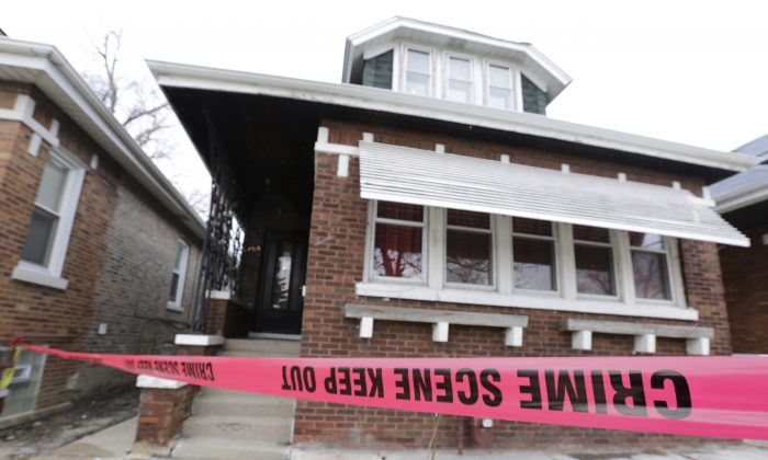 Crime scene tape surrounds a home Friday, Feb. 5, 2016, in Chicago. Chicago police are investigating what led to the deaths of two children, two women and two men whose bodies were found Thursday, with signs of trauma inside the home on the city's South Side. (AP Photo/M. Spencer Green)