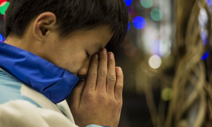 A young Chinese worshipper prays during the Christmas Eve mass at a Catholic church in Beijing on Dec. 24, 2014. (Fred Dufour/AFP/Getty Images)