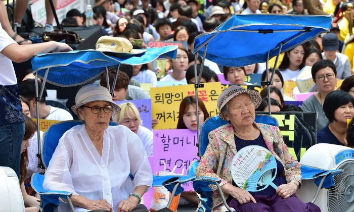 "South Korean former ""comfort women"" Kim Bok-Dong (L) and Gil Won-Ok (R), who were forced to serve as sex slaves for Japanese troops during World War II, attend a protest with other supporters to demand Tokyo's apology for forcing women into military brothels during World War II outside the Japanese embassy in Seoul on August 12, 2015. Close to 1,000 protestors had gathered outside the embassy ahead of the 70th anniversary of the end of Japan's 1910-45 colonial rule over the Korean peninsula.  AFP PHOTO / JUNG YEON-JE        (Photo credit should read JUNG YEON-JE/AFP/Getty Images)"