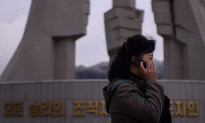 "A woman talks on a mobile phone before the ""Monument to Party Founding"" in Pyongyang on Oct. 11, 2015. (Ed Jones/AFP/Getty Images)"