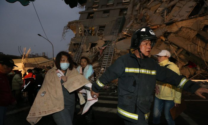 Rescue personnel and survivors at the site of a collapsed building in the southern Taiwanese city of Tainan following a strong 6.4-magnitude earthquake that struck the island early on February 6, 2016. (JOHNSON LIU/AFP/Getty Images)