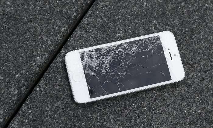 An Apple iPhone with a cracked screen after a drop test from the DropBot, a robot used to measure the sustainability of a phone to dropping, at the offices of SquareTrade in San Francisco on Aug. 26, 2015. Apple for the first time is accepting banged up iPhones as a trade-in from those wanting to upgrade. (AP Photo/Ben Margot)