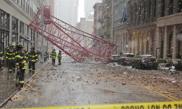 A collapsed crane lies along the street in New York on Feb. 5, 2016. The crane landed across an intersection and stretched much of a block in the Tribeca neighborhood, about 10 blocks north of the World Trade Center. (AP Photo/Bebeto Matthews)