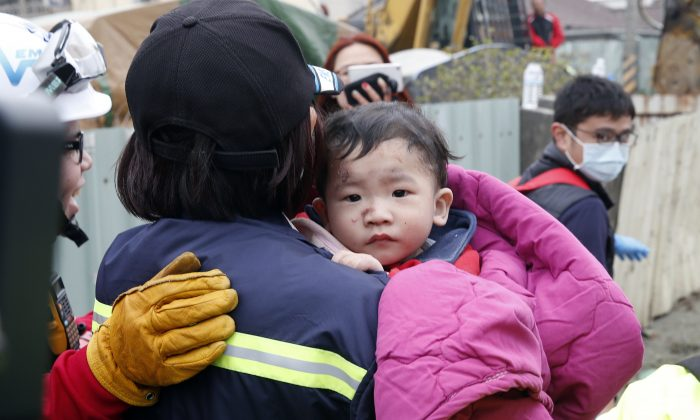 A baby boy is rescued from a collapsed building after an earthquake in Tainan, Taiwan, on Feb. 6, 2016. A powerful, shallow earthquake struck southern Taiwan before dawn Saturday. (AP Photo/Wally Santana)