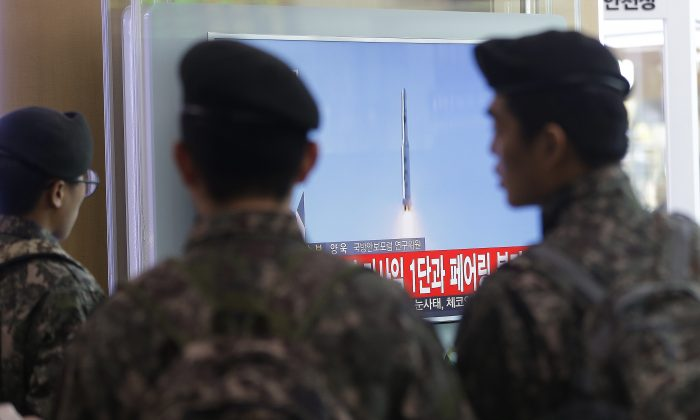 South Korean army soldiers watch a TV news program with a file footage about North Korea's rocket launch at Seoul Railway Station in Seoul, South Korea, Sunday, Feb. 7, 2016. (AP Photo/Ahn Young-joon)