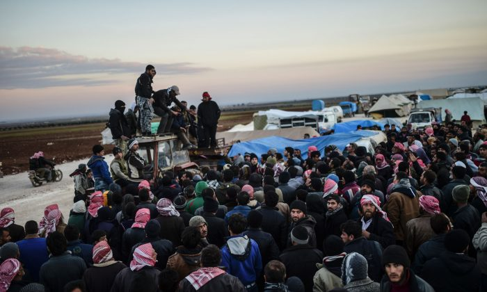 Syrians fleeing the northern embattled city of Aleppo wait on Feb. 5, 2016 in Bab-Al Salama, next to the city of Azaz, northern Syria, near Turkish crossing gate. Nearly 40,000 Syrian civilians have fled a regime offensive near Aleppo, a monitor said, as Turkey warned it was bracing for a wave of tens of thousands of refugees. (Bulent Kilic/AFP/Getty Images)