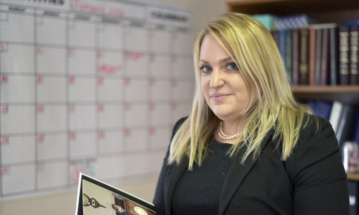 Amanda Grady Sexton, director of public policy for the New Hampshire Coalition Against Domestic and Sexual Violence, in her office in Concord, N.H., on Feb. 1, 2016. Sexton is holding a book of photos documenting efforts that led to the enactment of a state law that specifically created a domestic violence charge, allowing authorities to prevent those convicted of such crimes from buying or possessing a firearm. (AP Photo/Lisa Marie Pane)