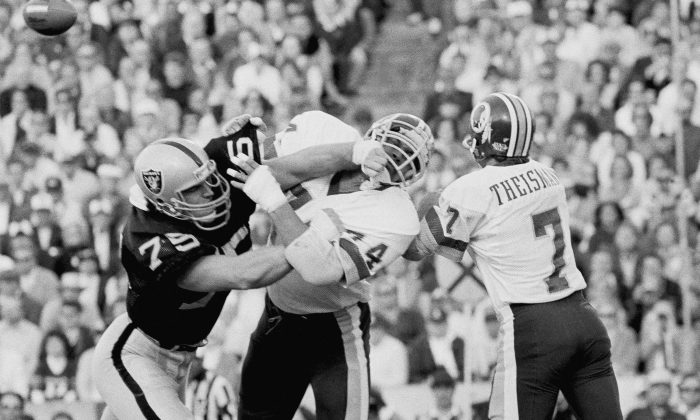 Los Angeles Raiders' Howie Long (L) battles Washington Redskins' George Starke next to Redskins quarterback Joe Theismann, who had just thrown a pass during the first half of NFL football's Super Bowl XVIII in Tampa, Fla., on Jan. 22, 1984. The magic that carried the Redskins vanished against Oakland. The Raiders and Marcus Allen stormed to a 38-9 victory that truly didn't feel that close. (AP Photo)