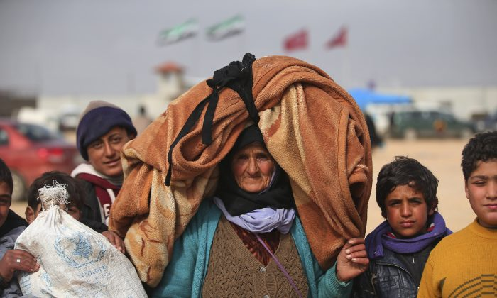 Syrians, some carrying belongings, head towards the Bab al-Salam border crossing with Turkey, in Syria, on Feb. 6, 2016. Thousands of Syrians have rushed toward the Turkish border, fleeing fierce Syrian government offensives and intense Russian airstrikes. Turkey has promised humanitarian help for the displaced civilians, including food and shelter, but it did not say whether it would let them cross into the country. (AP Photo/Bunyamin Aygun)