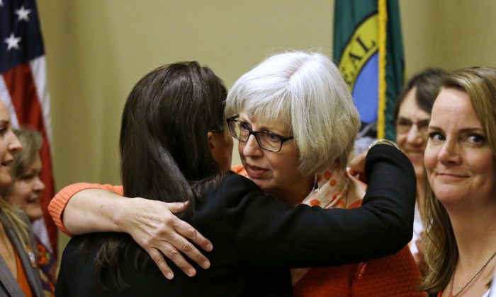 Jane Weiss, whose niece was shot and killed in the May 2014 shooting near the campus of UC Santa Barbara (R) is embraced by Cindy Gazecki, aunt of a high school shooting victim, following a news conference where they called on members of the Legislature to take action on proposed laws to help reduce gun violence in Olympia, Wash., on Jan. 21, 2016. Lawmakers in Washington state were to begin discussions later in the day on a list of gun-control measures that include requiring safe storage of firearms to avoid tragedies like the Marysville high school shooting and prohibiting law enforcement agencies from selling confiscated guns. (AP Photo/Elaine Thompson)