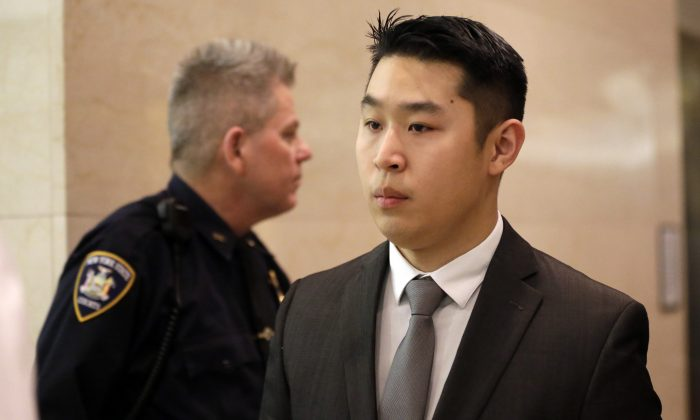 New York City rookie police officer Peter Liang, right, leaves the courtroom after his arraignment at Brooklyn Superior court, Wednesday, Feb. 11, 2015, in New York. (AP Photo/Mary Altaffer)