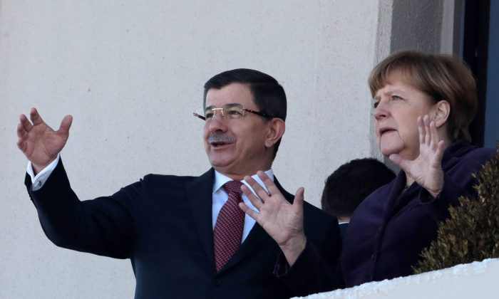 German Chancellor Angela Merkel (R) and Turkish Prime Minister Ahmet Davutoglu after a welcome ceremony in Ankara, Turkey, on Feb. 8, 2016. Merkel is meeting Davutoglu and other Turkish officials for talks on reducing the influx of migrants to Europe. Turkey, a key country on the migrant route to Europe, is central to Merkel's diplomatic efforts to reduce the flow. (AP Photo/Burhan Ozbilici)