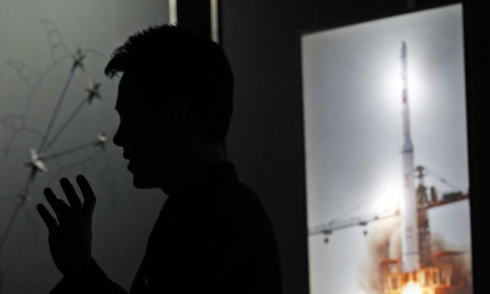 North Korean guide Kim Won Ho speaks near a photo depicting the 2009 satellite rocket launch at the Three Revolutions exhibition hall in Pyongyang, North Korea, on April 10, 2012. (AP Photo/Ng Han Guan)