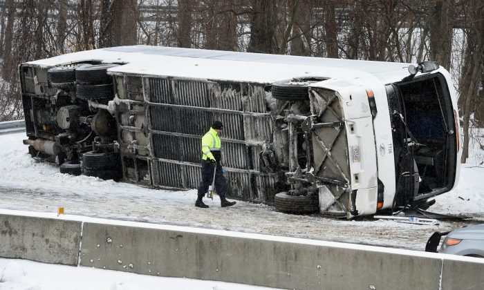A Connecticut State Police officer investigates an overturned casino-bound tour bus on I-95 North near exit 61 in Madison, Conn., on Feb. 8, 2016. At least 30 people were injured, several critically, in the accident. The bus was traveling from New York City to the Mohegan Sun casino in Uncasville, Conn. (Arnold Gold/New Haven Register via AP)
