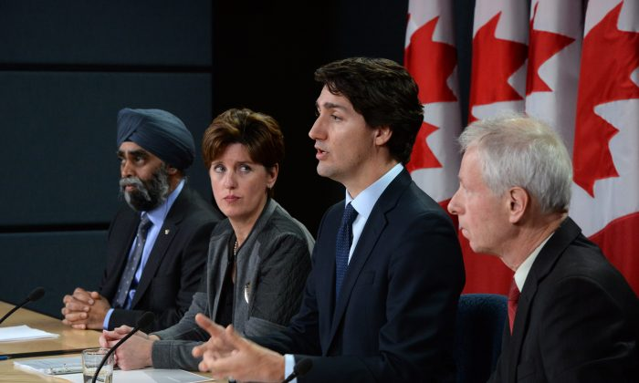 Canada's Prime Minister Justin Trudeau answers a question as he is joined by (L-R) Minister of National Defense Harjit Sajjan, Minister of International Development and La Francophonie Marie-Claude Bibeau and Minister of Foreign Affairs Stephane Dion at a news conference at the National Press Theatre in Ottawa on Feb. 8, 2016. (Sean Kilpatrick/The Canadian Press via AP)