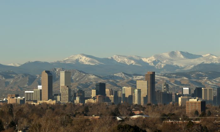 The Rocky Mountains rise beyond Denver skyline on Jan. 24, 2016. (AP Photo/Charlie Riedel)
