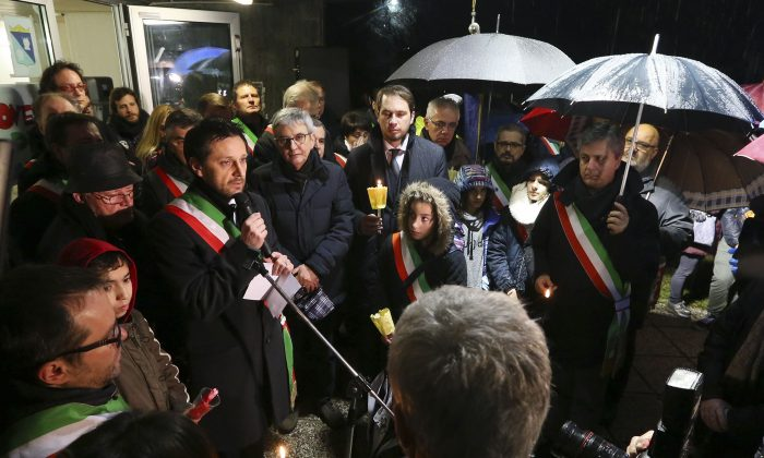 Fimuicello's Mayor Ennio Scridel delivers his speech during a candle lights procession to honor the memory of  Giulio Regeni in his hometown of Fiumicello, Italy, Sunday, Feb. 7, 2016. Regeni, 28, an Italian doctoral student disappeared in Cairo on Jan. 25, the anniversary of Egypt's 2011 uprising, a day when security forces were on high alert and on the streets in force to prevent any demonstrations or protests. His body, stabbed repeatedly and exhibiting cigarette burns and other signs of torture, was reported found on Feb. 3. (AP Photo/Paolo Giovannini)