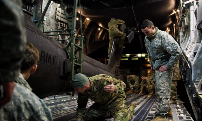 Soldiers and airmen work together to secure an AH-64 Apache helicopter onboard a C-17 Globemaster III on Pope Army Airfield, N.C., on Feb. 4. The new defense budget will make military service more attractive as a career. (Staff Sgt. Paul Labbe/U.S. Air Force)