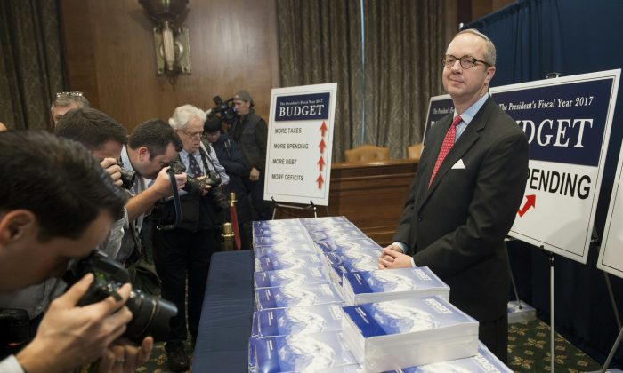 Eric Ueland of the Senate Budget Committee distributes copies of US President Barack Obama's Fiscal Year 2017 budget on Capitol Hill in Washington, DC, February 9, 2016. (SAUL LOEB/AFP/Getty Images)