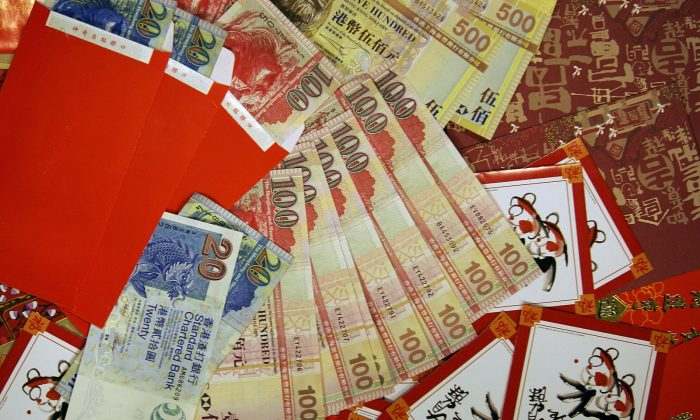 """Photo illustration shows newly minted Hong Kong Dollar banknotes (US$1 equivalent to HK$7.77) and """"lai see"""" or lucky money red packets in Hong Kong on Jan. 27, 2006. (Mike Clarke/AFP/Getty Images)"""