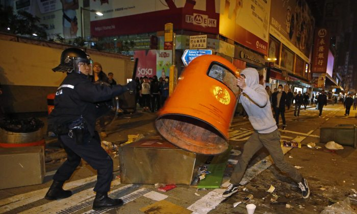 A rioter tries to throw a litter bin at police on a street in Mong Kok district of Hong Kong, Tuesday, Feb. 9, 2016. (AP Photo/Kin Cheung)