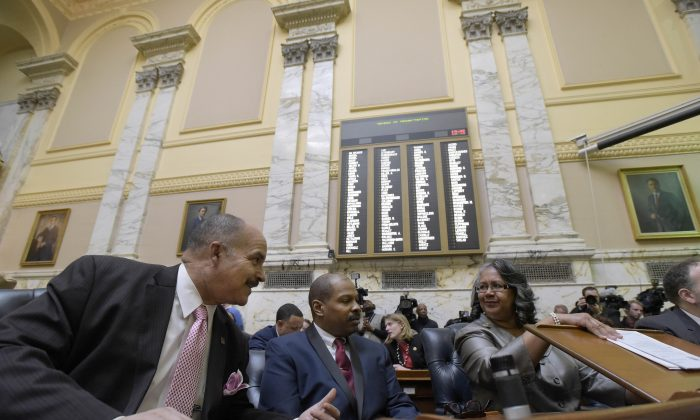 From left, Maryland Dels. Curtis S. Anderson, Frank M. Conaway Jr. and Cheryl D. Glenn confer as Maryland lawmakers gathered for the start of their annual 90-day legislative session, Wednesday, Jan. 13, 2016, in Annapolis, Md. (AP Photo/Steve Ruark)