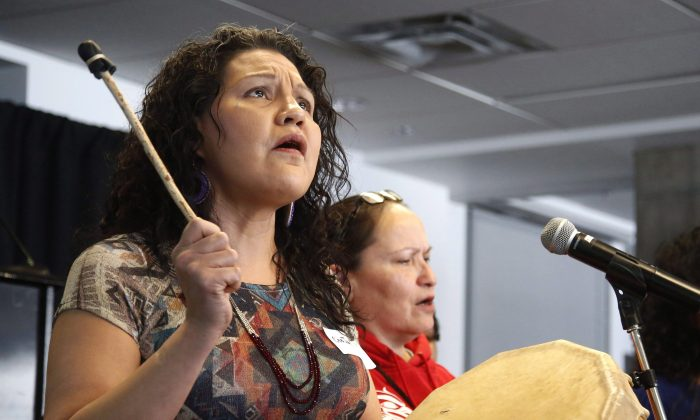 Cee Jai Julian, an aboriginal woman who escaped mass murderer Robert Pickton's farm, sings at the People's Gathering for Murdered and Missing Indigenous Women and Girls at Carleton University in Ottawa on Feb. 27, 2015. Indigenous Affairs Minister Carolyn Bennett recently met with the families of missing and murdered aboriginal women in Winnipeg, and said she noticed a different tone from similar meetings in other cities. (The Canadian Press/ Patrick Doyle)