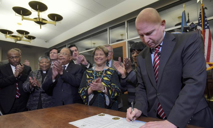 Delaware Gov. Jack Markell, right, signs House Joint Resolution 10, which apologizes for the state's role in slavery, Wednesday, Feb. 10, 2016, at the Delaware Public Archives in Dover, Del. Markell also presented a proclamation recognizing African American History Month. (AP Photo/Steve Ruark)