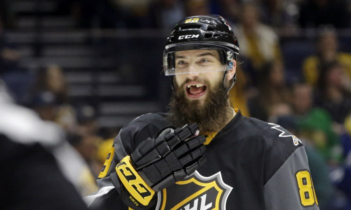 "In this Sunday, Jan. 31, 2016, file photo, Pacific Division defenseman Brent Burns (88), of the San Jose Sharks, talks with a referee during the NHL hockey All-Star championship game in Nashville, Tenn. When Brent Burns packs his bags for road trips, the Sharks defenseman usually leaves some cosmetic teeth behind. ""I don't wear them often,"" he said. ""I usually find them in a drawer a couple months down the road and put them somewhere safe, forget where that is, and find them a couple months later."" (AP Photo/Mark Humphrey, File)"
