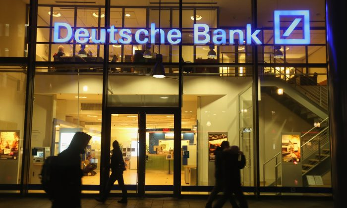 People pass by the Deutsche Bank branch in Berlin, Germany on February 9, 2016.  (SeanGallup / Getty Images)